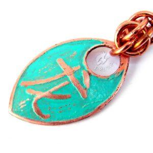 Miedziane kolczykiz wytrawianym chińskim symbolem smoka, pokryte patyną, zbliżenie na symbol