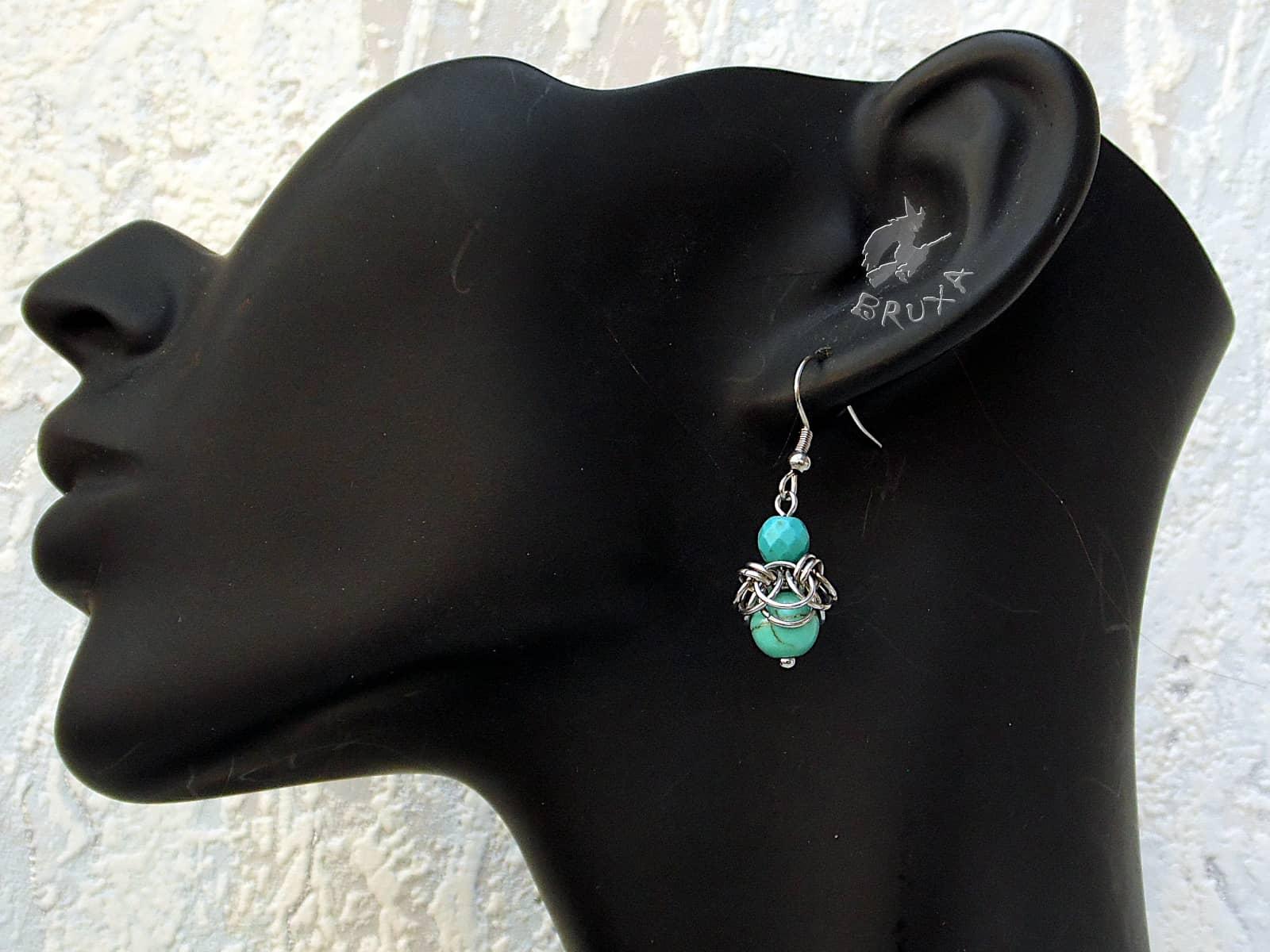 Kolczyki Gloria stalowe z turkusowym howlitem zaprezentowane na uchu ekspozytora